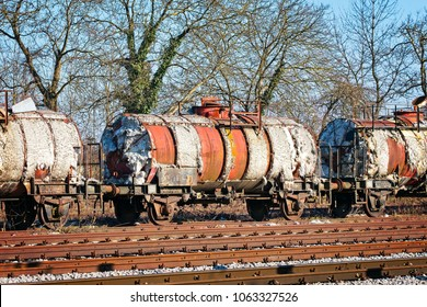 Degraded wagons with asbestos insulation on  the side track of local railway station waiting to be recycled.
