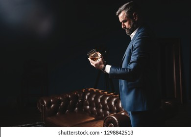 Degustation, tasting. Man with beard holds glass of brandy. Tasting and degustation concept. Bearded businessman in elegant suit with glass of whiskey. Sommelier tastes expensive drink.