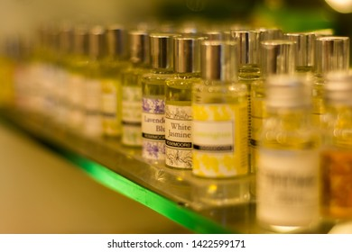 Dehradun, India - January 28, 2019: Glass bottles of essential oils kept on a glass shelf in a store lit by a warm light. White jasmine and lavender blue are in focus. Background is blurred.