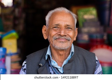 Dehradun, India-January 28, 2019: an old Indian man smiling and looking at the camera. he has a wrinkled face and is wearing winter clothes. he is half bald and has grey hairs. background is blurred.