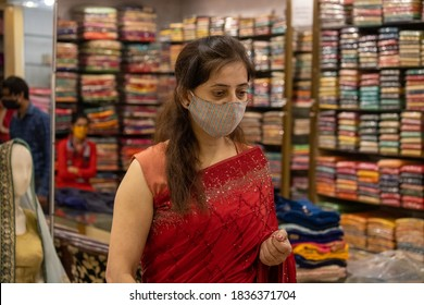 Dehradun, Uttarakhand/India-October 14 2020:A Beautiful Indian lady in saree wearing face mask for Shopping in India, Mask is mandatory due to corona pandemic. High quality photo