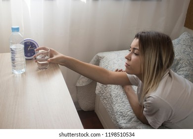 Dehydrated woman reaches for a glass of water