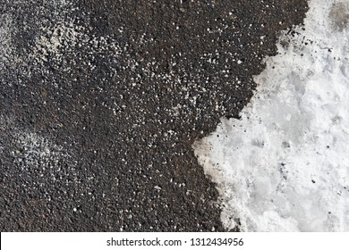 De-icing chemicals on the asphalt road. Pavement is sprinkled with technical salt or salt mixtures based on it. Reagent - technical salt will make the road safe. Effective tool to fight ice on roads