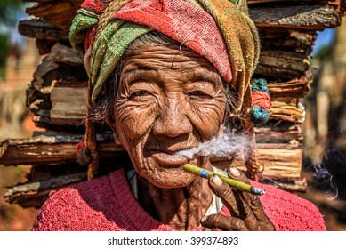 IN DEIN, MYANMAR - JANUARY 27, 2016 : old wrinkled woman smokes  a cheroot cigar