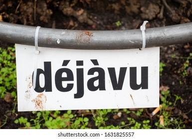 Deja by sign in dirty urban street