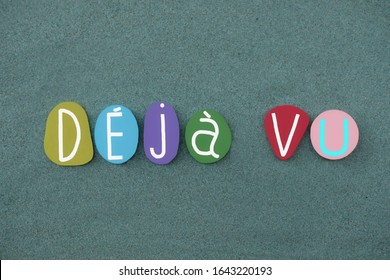Deja vu, neurological anomaly text composed with multi colored stone letters over green sand