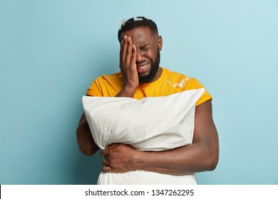 Dejected crying man covers face with hand, has thick stubble, dressed in yellow t shirt, has problems with sleep, carries white pillow, isolated over blue background. Sleeping and depression