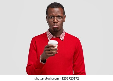 Dejected dissatisfied guy has dark skin, miserable facial expression, purses lips in discontent, drinks take out coffee, wears optical glasses and red jumper, isolated over white background.