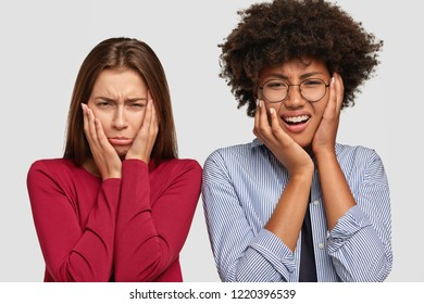 Dejected sad two diverse women have miserable expressions, cry desperately, have misfortune and problems, stand closely against white background. African American girl and her sister feel unhappy