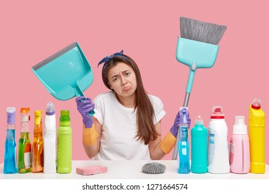 Dejected upset young housemaid frowns face in discontent, holds scoop and broom, does cleaning, wears headband and t shirt, isolated over pink background. Domestic routine and busyness concept