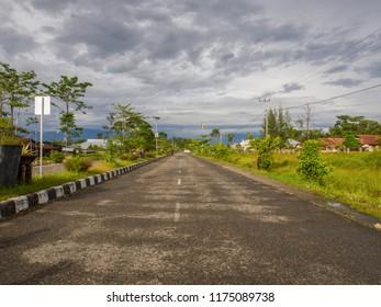 Dekai, Indonesia - January 12, 2015: Black,  asphalt road stretching  up to  horizon. West Papua.