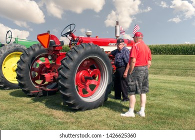 Dekalb County, IL / USA - August 11, 2018: Two old farmers walking while standing front of a display of antique tractors.