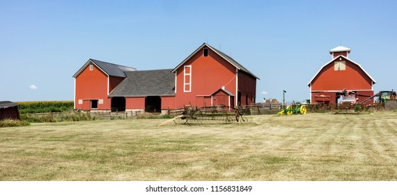 Dekalb County, Illinois / USA - August 11, 2018: A traditional, family farm displays antique farming equipment during a barn tour. Bright red, old barns and corn crib stand out against blue sky.