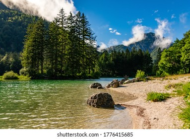 """""""Lago del Predil"""" or """"Raibler See"""" is a green mountain lake near Tarvisio, Austria and Slovenia in a valley of the Julian alps with pine trees, island and beautiful reflection on a sunny summer day"""