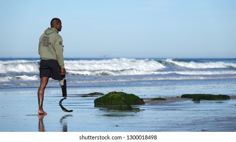Del Mar, CA / USA - January 27, 2019: A man (likely an injured veteran) with a Flex-Foot prosthesis walks on the beach