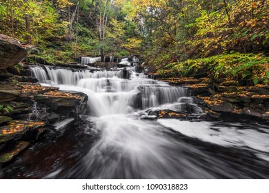 Delaware Falls, a beautiful waterfall in Pennsylvania's Ricketts Glen State Park, is surrounded by colorful fall foliage.
