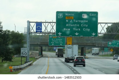 Delaware, USA- September 2017: Directional signs on the interstate highway with directions to New York City and Atlantic City on a rainy day.