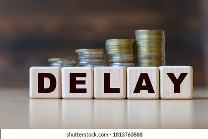 DELAY word on diced on a beautiful dark background with coins. Business concept