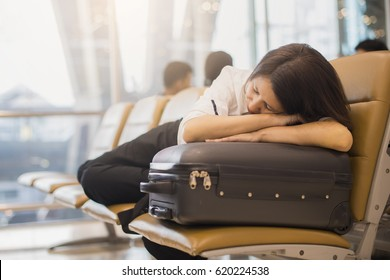 Delayed airplane concept. Tired Asian woman is sleeping on luggage in airport terminal and waiting for airplane arrival.
