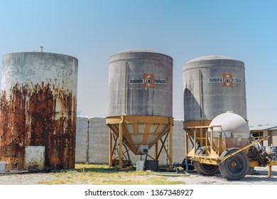 DELCAMBRE, L.A. / APRIL 10, 2019: Industrial tanks holding feed and other materials are next to each other in a field in Delcambre, Louisiana.