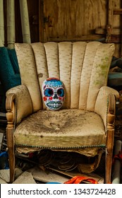 DELCAMBRE, L.A. / USA - MARCH 14, 2019:  Mexican and Spanish Sugar skull painted mask and decoration for the spirits in the tradition of Día de Los Muertos. Day of the dead skull on an old chair.