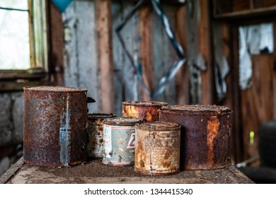 DELCAMBRE, L.A. / USA - MARCH 14, 2019: Antique rusted tin paint cans.  Antique, vintage, rusted spray paint can found in an abandoned workshop. Old paint container bucket. Wood paint and stain bottle