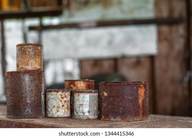 DELCAMBRE, L.A. / USA - MARCH 14, 2019: Antique rusted tin paint cans.  Antique, vintage, rusted paint can found in an abandoned workshop. Old paint container bucket. Wood paint and stain dried up.