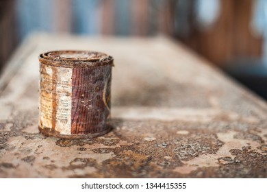 DELCAMBRE, L.A. / USA - MARCH 14, 2019: Antique rusted tin paint cans.  Antique, vintage, rusted motor oil and paint can found in an abandoned workshop. Old paint container bucket.