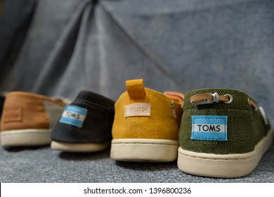 DELCAMBRE, L.A. / USA - MAY 08, 2019: Toms shoes. A pile of Toms flats, slip on, women's and kids footwear spread out on the floor.
