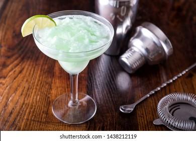 A delcious frozen lime daiquiri on a wooden bar counter top.