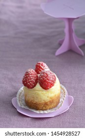 Delectable mini raspberry cheesecake on pink cupcake stand on pale mauve linen background. Selective focus on front raspberries. Horizontal format.