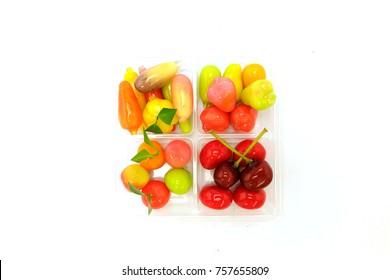 Deletable Imitation Fruits on the Plastic Box Isolated on white background.