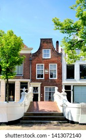 """DELFT, HOLLAND-MAY 31, 2019: Canal house in Delft and  white bridge on the Voorstraat .The house is  called """"De vergulde noot"""" that means the """"The gold plated nut"""" with a facade stone above the entran"""