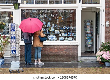 DELFT, NETHERLANDS - 25 AUGUST, 2018: Two tourists with red umbrella looking at window display of traditional Dutch hand painted pottery shop in Delft, Netherlands