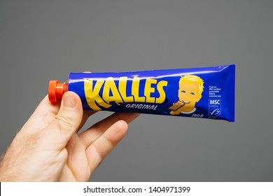 Delft, Netherlands - Apr 6, 2019: Male hand holding tube with Kalles origianl caviar. Kalles Kaviar is a Swedish brand of smorgaskaviar - isolated on gray background horizontal