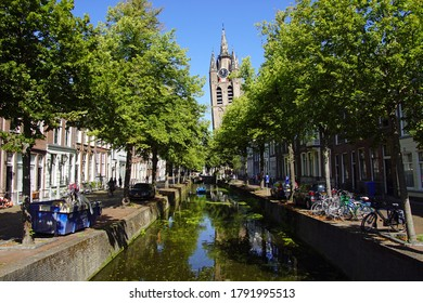 Delft, the Netherlands - August 5, 2020: The Oude Delft canal and leaning tower of Gothic Protestant Oude Kerk in the picturesque Dutch historical city of Delft.