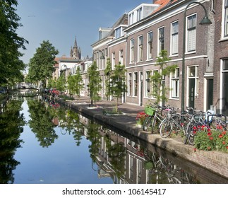 Delft, The Netherlands: church towers and houses reflected in canals on a beautiful summer day