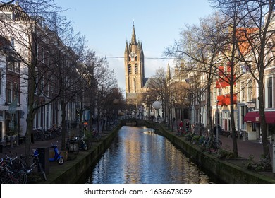 """Delft, the Netherlands, Holland,January 18, 2020. view of a canal and the leaning bell tower of the Oude Kerk (Old church), (""""Old John""""), a Gothic Protestant 12th century church in the old city center"""