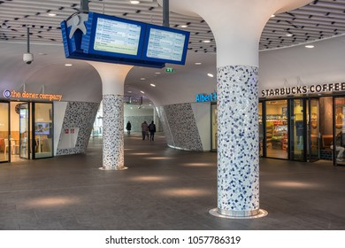 Delft, The Netherlands - march 15, 2018: Travellers in concourse of new railway station Delft with modern art ceiling, shops and information panel
