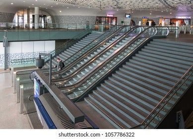 Delft, The Netherlands - march 15, 2018: Concourse of new railway station Delft with modern art ceiling and travellers at stairs and escalator