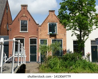 DELFT, NETHERLANDS- MAY 31 2019: Typical Dutch old canal houses in Delft and beautiful small white bridge on the Geerweg
