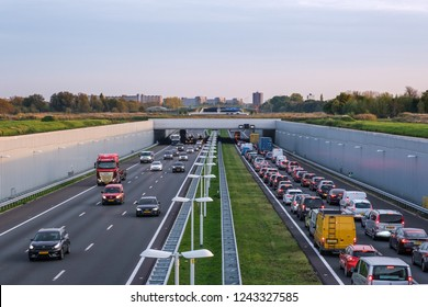 DELFT, NETHERLANDS - OCT 31, 2018 : Modern deepened highway A4, afternoon traffic jam. Highway leading under a green bridge and aqueduct of a nature reserve, close to Rotterdam Netherlands.
