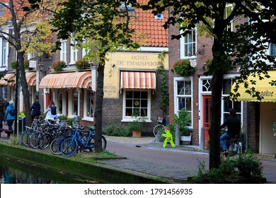 Delft, The Netherlands - October 10, 2019: By the houses in historical part of the city, bikes have been parked at the edge of the canal.