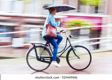 DELFT, NETHERLANDS - SEPTEMBER 04, 2015: unidentified cyclist on a rainy day. In NL almost as many kilometres are covered by bicycle as by train. It is estimated that they have at least 18 mio bicycle