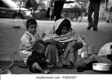 DELHI - DECEMBER 21: A mother feeds her children what little they have to eat (in the road) on December 21, 2009 in Delhi, India. More than 37% of the people in India live below the poverty line.