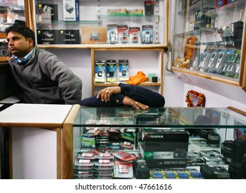 DELHI - FEBRUARY 5: Sleeping salesman waiting headlessly for customers on February 5, 2008 in Delhi, India. Chadni Chawk camera market is the largest in India.