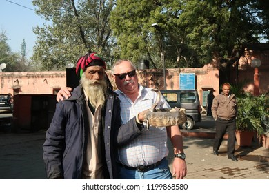 Delhi, India. 10/10/2018. An American touris handling a King cobra with a snake charmer