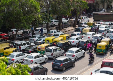 DELHI, INDIA - 19TH MARCH 2016: Large amounts of traffic on a road in India during the day. Tuk Tuk Rickshaws, motorbikes, cars and people can be seen.