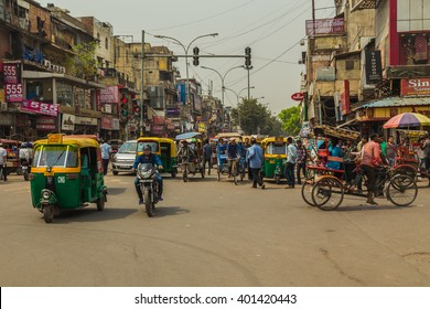 DELHI, INDIA - 19TH MARCH 2016: A view along streets of Delhi during the day showing buildings, Tuk Tuk Rickshaws, motorbikes and people.