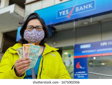 Delhi, India : 2020 Portrait of a young Indian woman wearing a face mask to avoid coronavirus, counting cash outside financial crisis a Yes Bank. There have been restrictions put on withdrawal limit